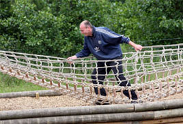 Parent climbing across rope bridge at CONKERS